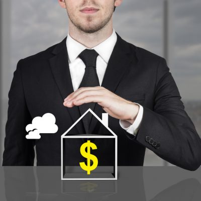 businessman in office holding protective hand above house dollar symbol