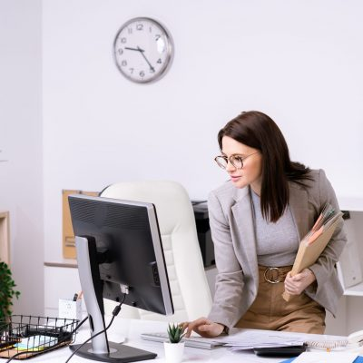 Brunette businesswoman in jacket standing at desk and shutting down computer while leaving office