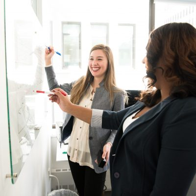 women drawing succession plan on whiteboard